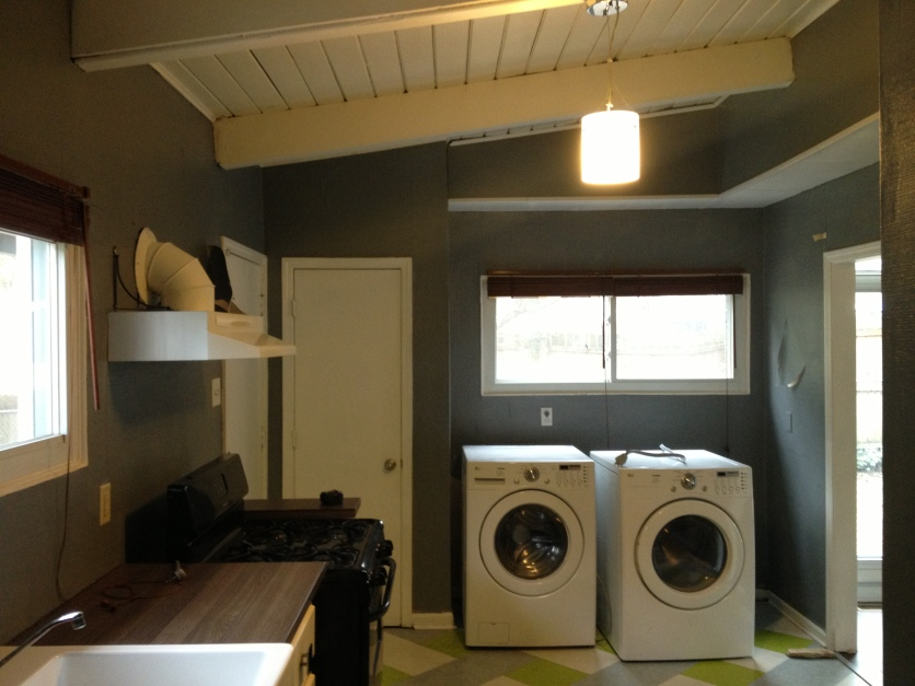 kitchen entry before with pantry and laundry. The washer and drier combo was left by the previous owners.